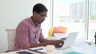 Businessman Working At Desk In Design Studio