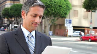 Businessman Working On Tablet Computer Outside
