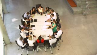 Businesspeople Leaving At The End Of Meeting Around Table
