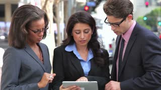 Businesspeople Using Digital Tablet Outside