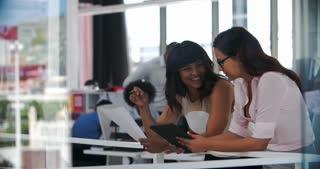 Businesswomen Having Informal Meeting In Open Plan Office