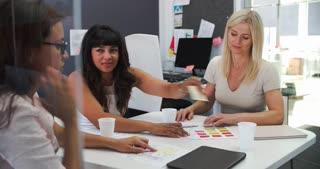 Businesswomen Having Meeting In Open Plan Office