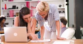 Businesswomen Working On Laptop In Busy Office