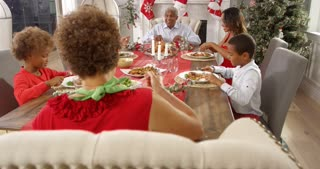 Camera tracks around table as extended family group enjoy Christmas meal together