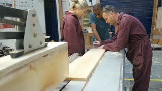 Carpenter Showing Apprentices How To Measure Wood
