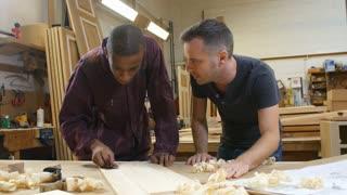 Carpenter With Apprentice Sanding Wood In Workshop