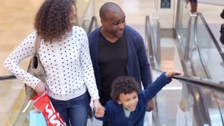 Child On Trip To Shopping Mall With Parents On Escalator