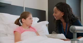 Child Patient In Bed Talking To Doctor In Hospital Room