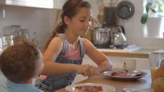 Children At Home Eating Pancakes For Breakfast In Kitchen