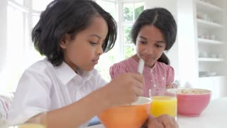 Children Having Breakfast In Kitchen Before School