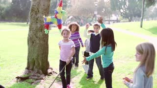 Children Hitting Pinata At Birthday Party In Slow Motion