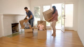 Children In New Home Playing With Boxes On Moving Day