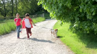 Children Running Along Country Path With Dog