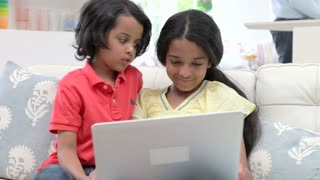 Children Using Laptop Whilst Sitting On Sofa At Home