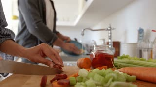 Close in shot of couples� hands chopping food and washing up, shot on R3D