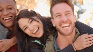 Close up handheld pan of three couples piggybacking outdoors
