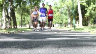 Close Up Of Feet As Group Of Runners Jog Through Park
