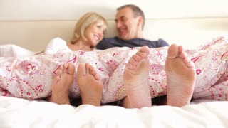 Close up of feet wriggling as senior couple sit up and chat in bed.Shot on Canon 5D Mk2 at at a frame rate of 30 fps