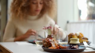 Close Up Of Food As Woman Enjoys Meal In Restaurant