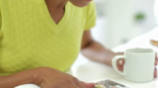 Close Up Of  Woman Eating Breakfast And Reading Magazine