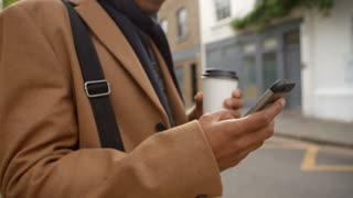 Close Up Of Young Man Using Phone On Busy City Street