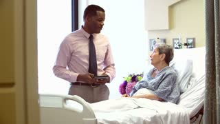 Consultant Talks To Senior Female Patient In Hospital Room