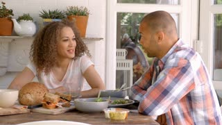 Couple At Home Eating Meal On Outdoor Verandah Together