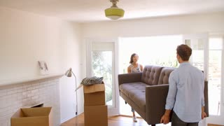Couple Carrying Sofa Into New Home On Moving Day