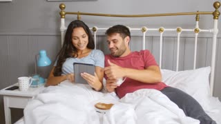 Couple Eating Breakfast In Bed Whilst Using Digital Tablet