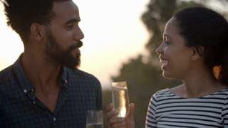 Couple Enjoying Glass Of Champagne Outdoors Together