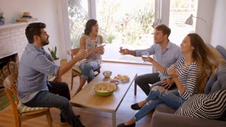 Couple Entertaining Friends At Home Shot In Slow Motion