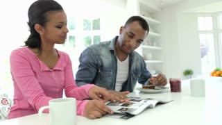 Couple Having Breakfast And Reading Magazine In Kitchen