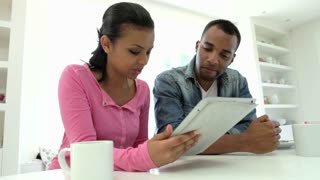 Couple Having Breakfast And Using Digital Tablet In Kitchen