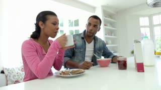Couple Having Breakfast In Kitchen Together