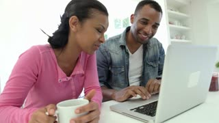 Couple Having Breakfast Using Laptop In Kitchen Together