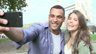 Couple Taking Selfie By Tower Bridge In London