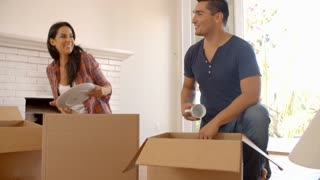 Couple Unpacking Boxes In New Home On Moving Day