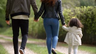 Couple walk with young daughter in a country lane, back view