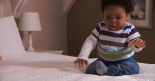 Cute Baby Having Fun Bouncing On Parents Bed