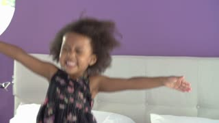 Cute Little Girl Jumping On Parent's Bed