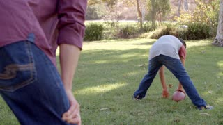 Dad and son passing American football to each other in park