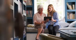 Daughter Helping Senior Mother With Digital Tablet At Home