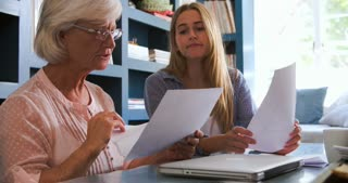 Daughter Helping Senior Mother With Paperwork In Home Office