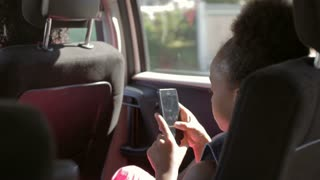 Daughter Playing Game On Mobile Phone During Car Journey