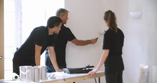 Decorator instructing colleagues painting room with rollers