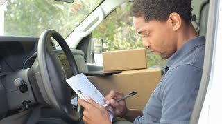 Delivery Driver Sitting In Van Filling Out Paperwork