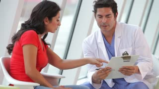 Doctor Discussing Notes With Female Patient