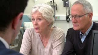 Doctor Having Discussion With Senior Couple In Surgery