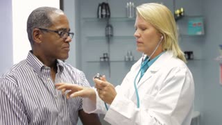 Doctor Listening To Male Patient's Chest With Stethoscope