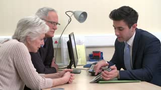 Doctor Shows Results To Senior Couple On Tablet Computer